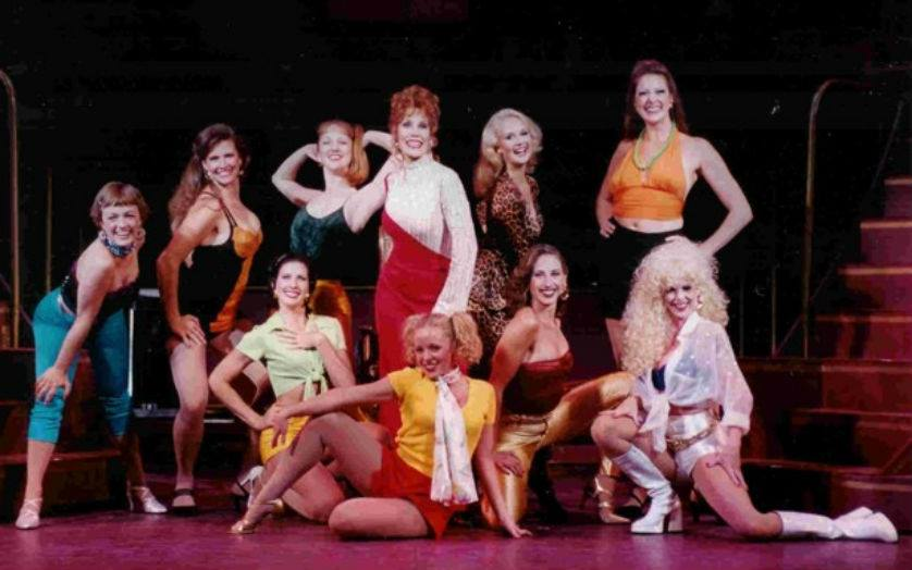"Miss Mona (Paty Lombard) surrounded by the residents of ""The Best Little Whorehouse in Texas,"" directed and choreographed by Scott Thompson for Austin Musical Theatre in 2001."
