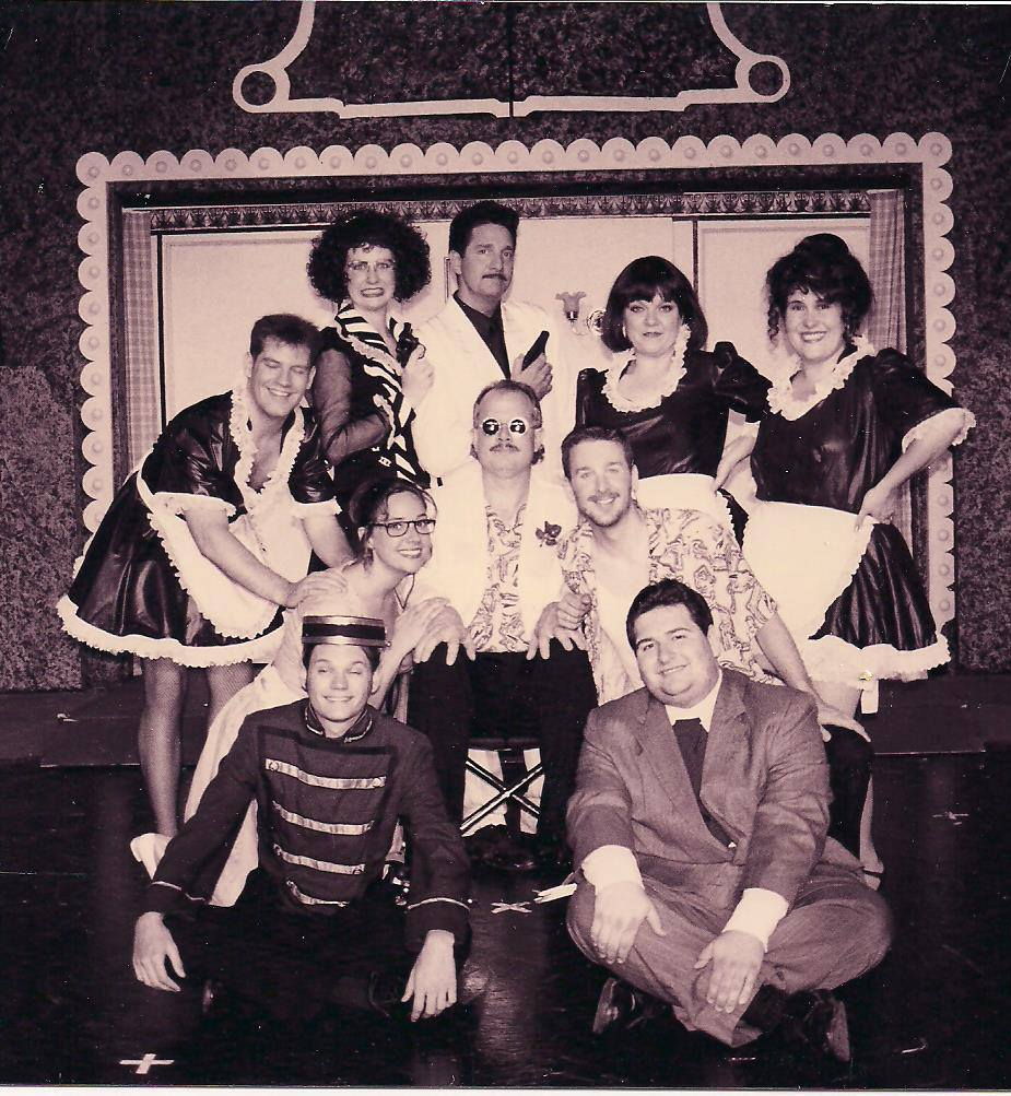 "Theater Work's 1998 production of ""Lucky Stiff"" featured First Row: Unidentified Actor, Chris Wo. 2nd Row: Shana Rebilas Bousard, Paul Black, Dominik Rebilas. 3rd Row: John Haubner, Dina Kay Mountcastle, Joe Marshall, Jacque Howard Hemstreet and Johanna Carlisle. (Photo credit unknown; photo posted on Facebook by Rachel Cohen)"
