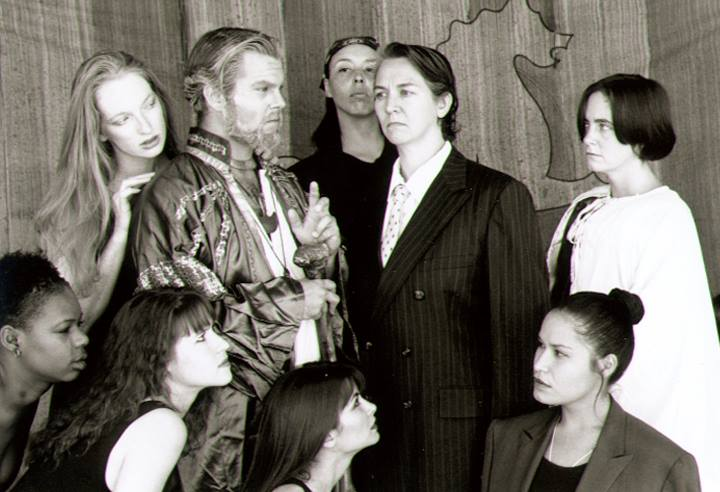 "Suze St. John (in suit) as the King of Naples was one of many male roles essayed by women in Planet Earth Theatre's gender-bending 1996 production of ""The Tempest."" (Photo from the collection of Mollie Kellogg)."